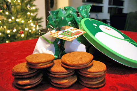 Molasses sandwich cookies with holiday decorations behind them