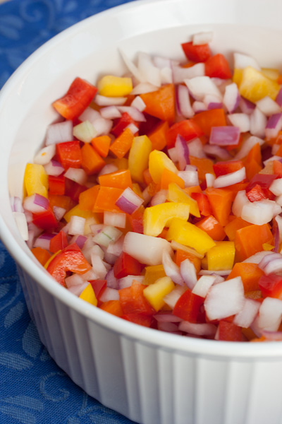 Bowl of colorful chopped bell peppers and onions.