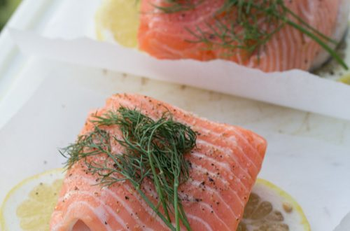 Salmon on parchment paper squares with lemon and fresh dill