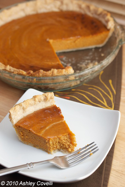 Pumpkin pie with a slice on a plate and a bite taken out of it.