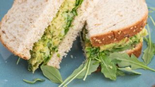 A sandwich that is filled with an avocado and chickpea mixture and baby arugula, sliced in half on a blue plate.