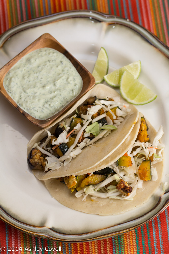A plate of Roasted Kabocha and Eggplant Tacos with Poblano Crema and lime wedges.