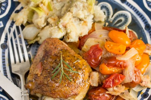 Overhead view of a plate with chicken thighs covered in a pan sauce and fresh rosemary next to colorful tomatoes and mashed potatoes.