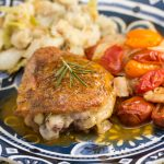 3/4 view of a plate with chicken thighs covered in a pan sauce and fresh rosemary next to colorful tomatoes and mashed potatoes.