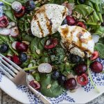 Overhead view of a plate of salad topped with fruit, vegetables, and burrata cheese drizzled with aged balsamic.