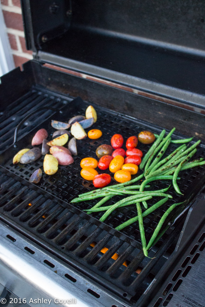 A grill with colorful potatoes, tomatoes, and green beans.