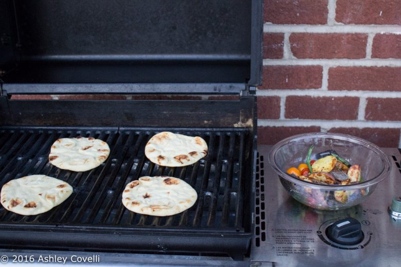 A grill with mini naan breads on top and a bowl of grilled veggies off to the side.