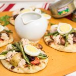 3 mini naan breads topped with grilled Niçoise salad ingredients along with a pitcher of vinaigrette and tuna cans in the background.