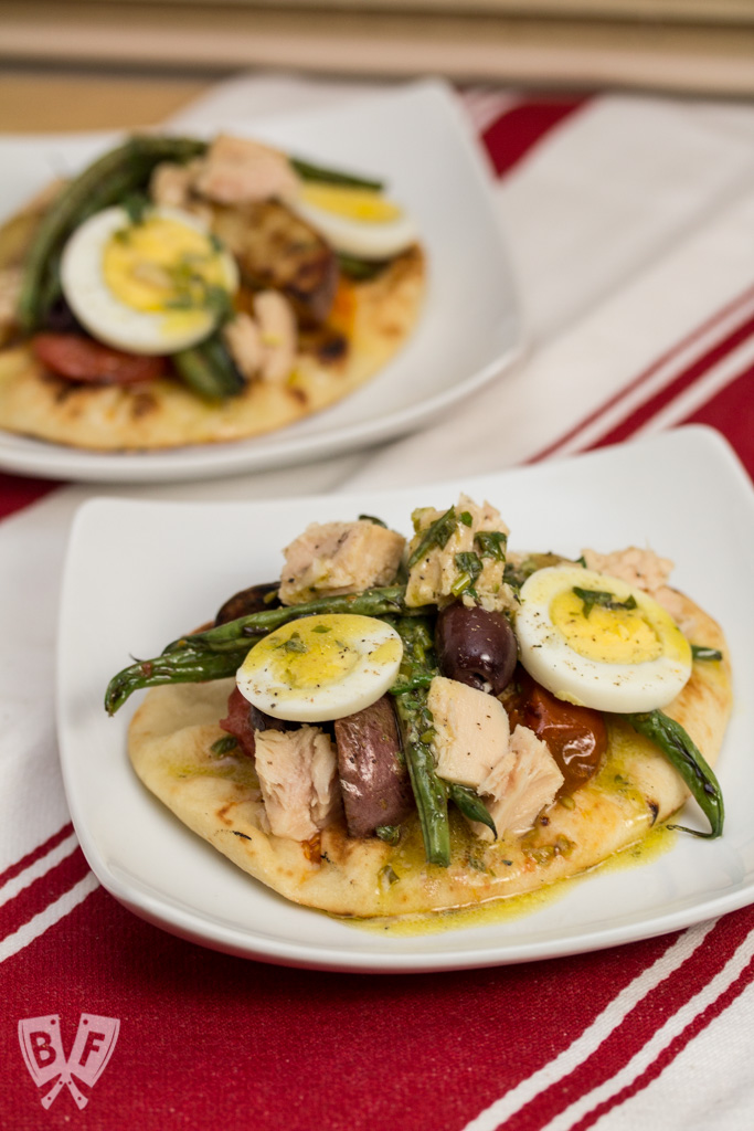Mini naan breads topped with grilled Niçoise salad ingredients.