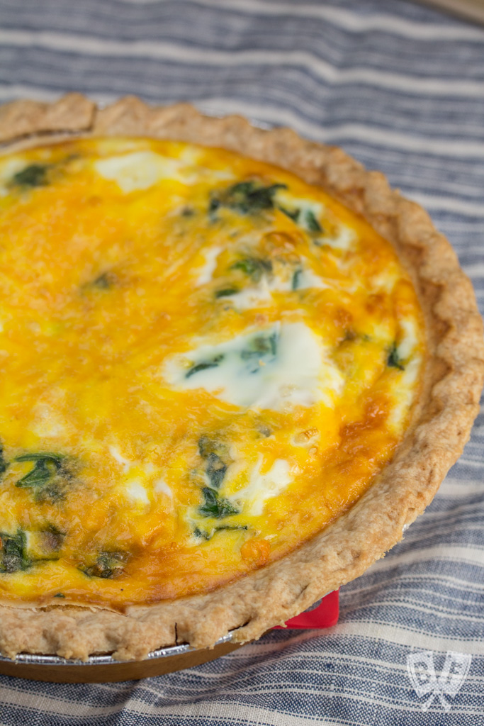 Overhead view of a full baby spinach and cheddar quiche
