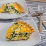2 plates with slices of baby spinach and cheddar quiche