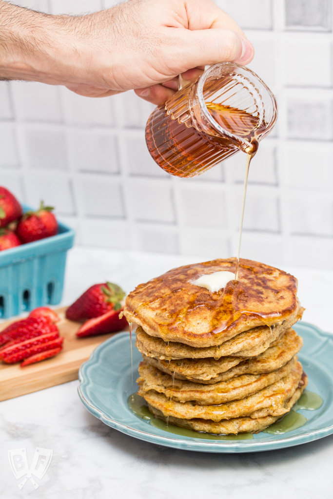 Pouring syrup onto a stack of buttermilk pancakes