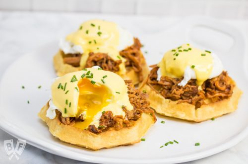 A platter with 3 waffles topped with pulled pork, poached eggs, hollandaise sauce, and chives.