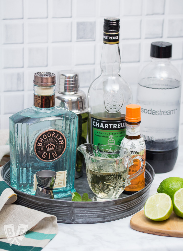 A tray with bottles of ingredients for a gin cocktail with garnishes off to the side.