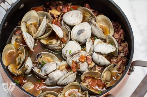 Garlicky Littleneck Clams with Bacon + Wine Over Sautéed Spring Veggies: A bed of sautéed veggies makes the perfect base for this bacon-loaded seafood dish. Make sure you have plenty of crusty bread for dunking! #BaconMonth