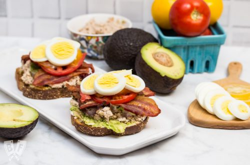 Side view of a platter with 2 open-faced TABLET Sandwiches (Tuna Avocado Bacon Lettuce Egg Tomato) and ingredients off to the sides.