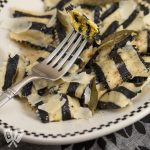 Overhead view of a plate of black and white striped sweet potato ravioli - a tribute to Beetlejuice