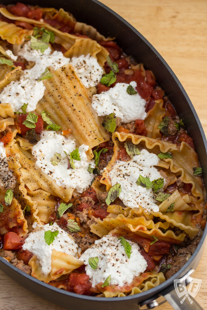 Overhead view of a skillet lasagna with lamb, ricotta, and mint.
