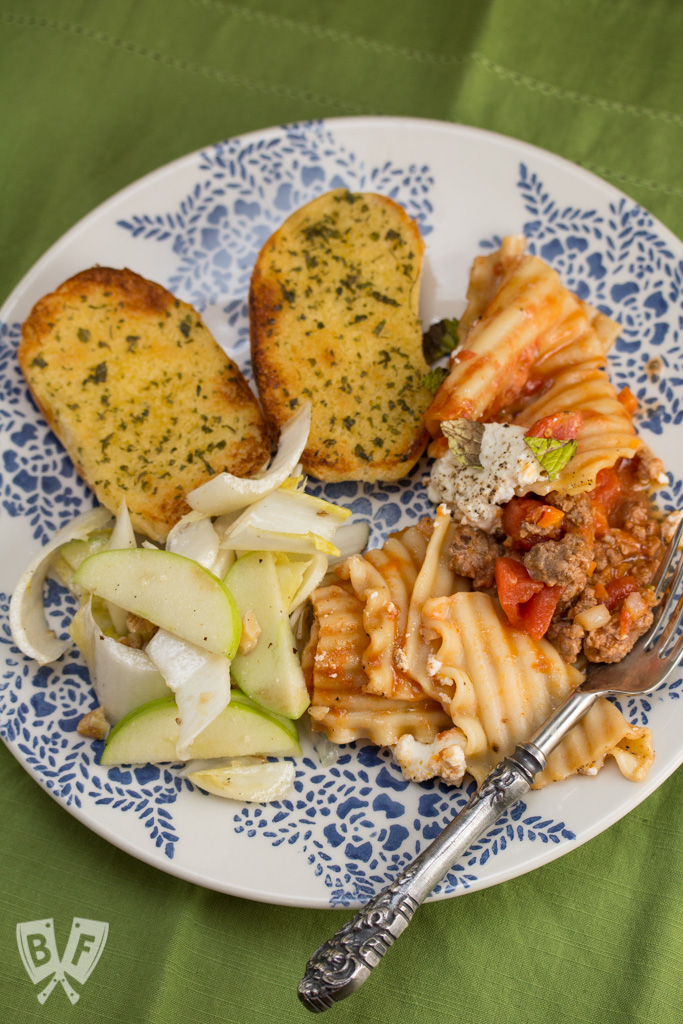 Overhead view of a plate with lamb lasagna, garlic bread, and endive salad with apples.