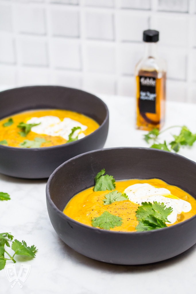 Side view of 2 bowls of curried pumpkin soup with cilantro leaves, sour cream, and chili oil garnish.