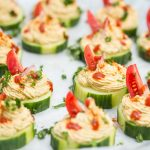 Close up of a few cucumber slices topped with a spiced chickpea purée.