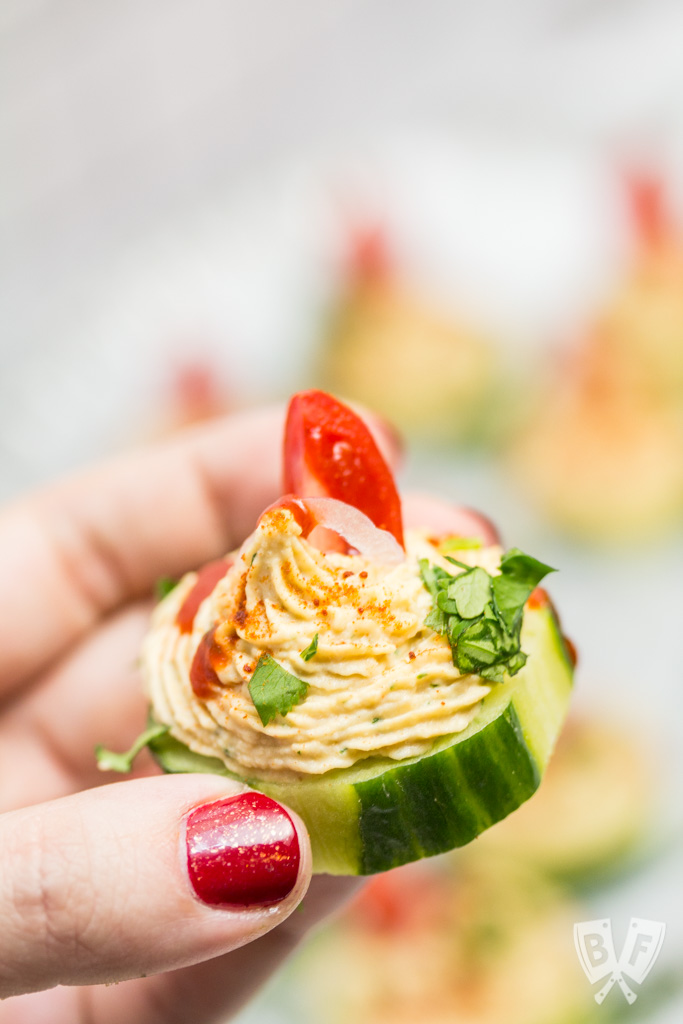 Close up of a hand holding a cucumber slice topped with a spiced chickpea purée with a platter out of focus in the background.