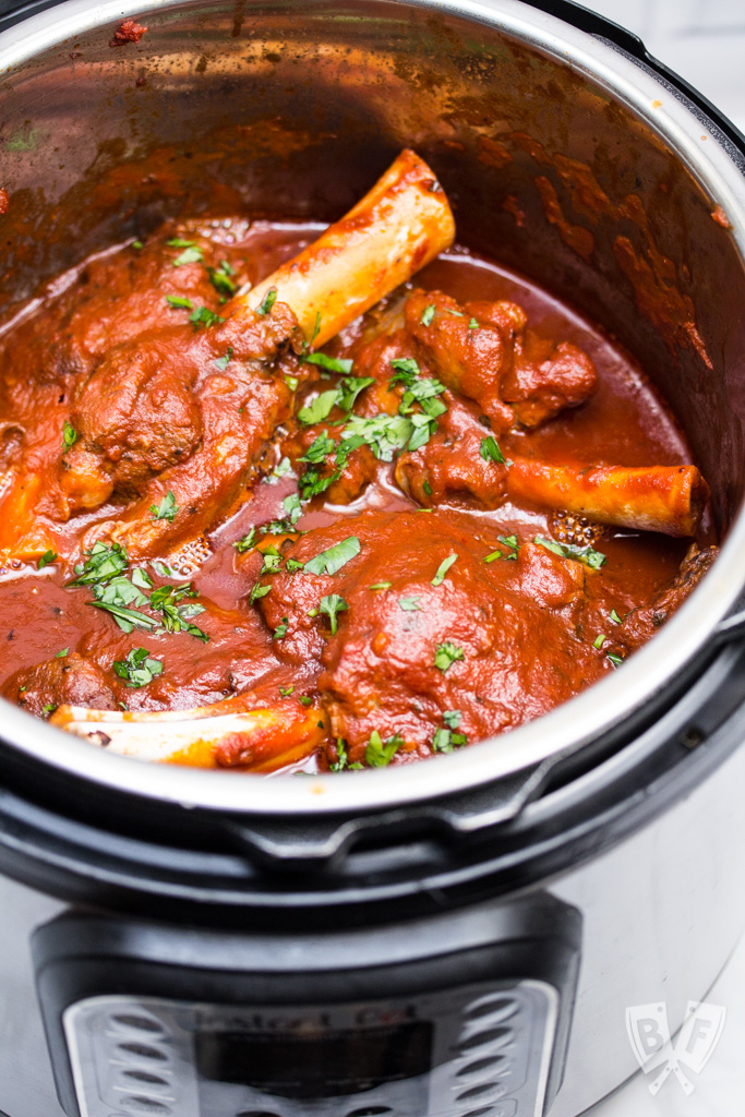 Overhead shot of lamb shanks with tomato sauce in an Instant Pot.