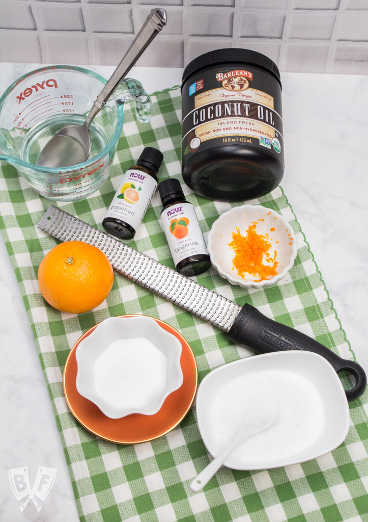Overhead view of the products and tools used to make a homemade citrus salt scrub.