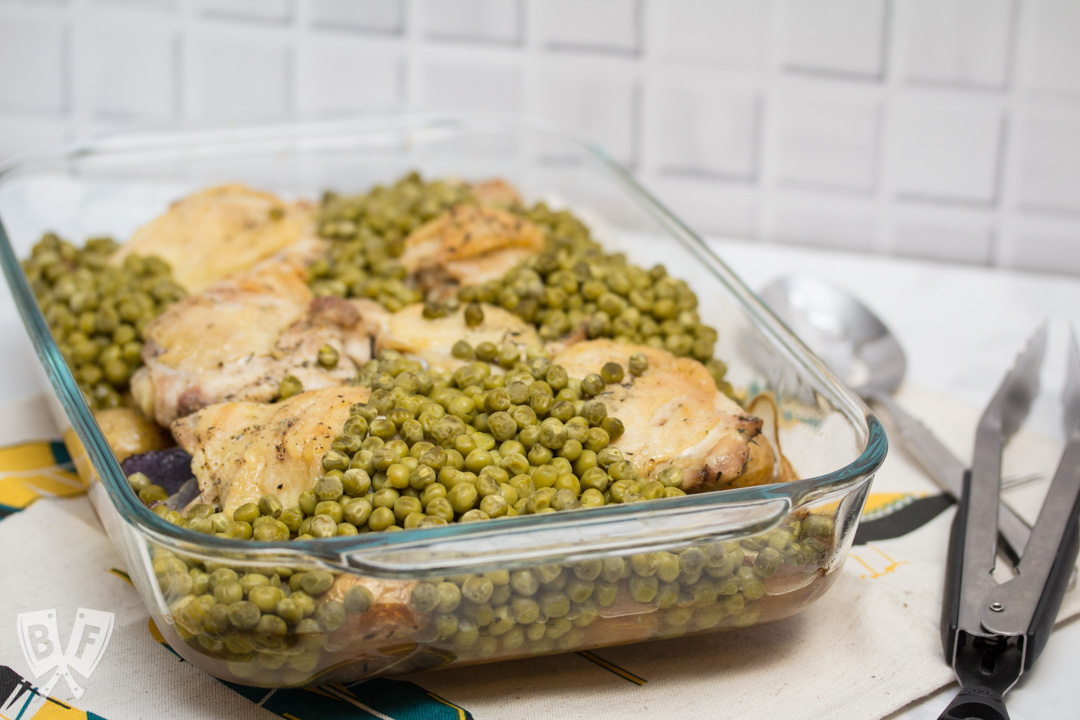 3/4 view of a casserole dish filled with baked chicken thighs, peas, and potatoes with tongs and a serving spoon.