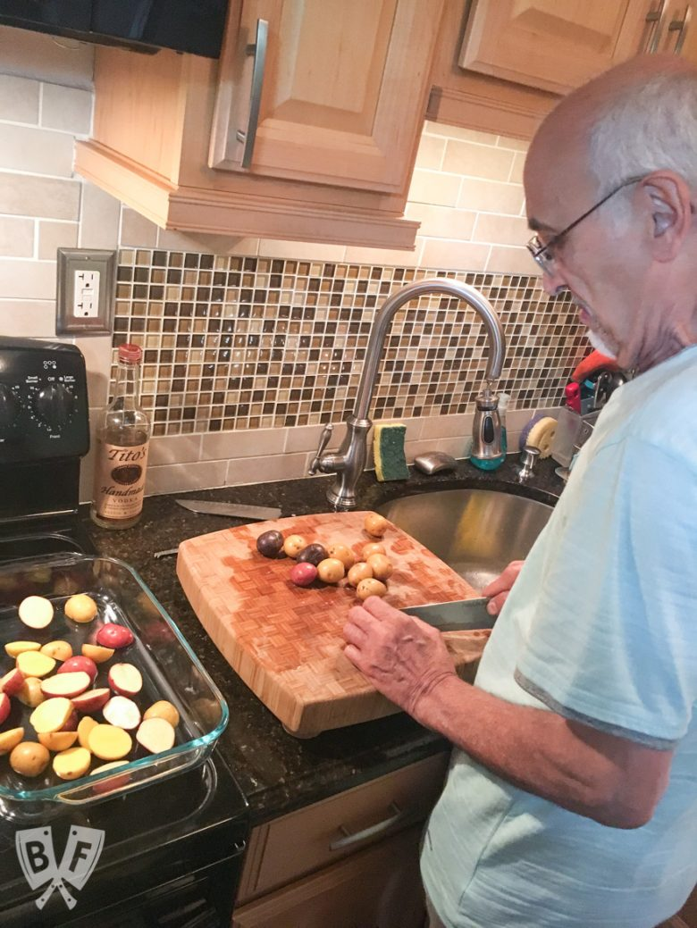 Over-the shoulder photo of a man in a kitchen cutting potatoes and placing them into a casserole dish.