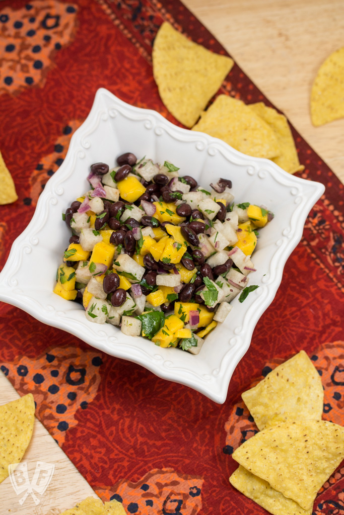 Overhead shot of a bowl of Mango, Jicama + Black Bean Salsa with tortilla chips.