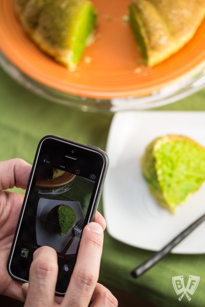 Hands taking a photo with a phone of a green bundt cake on a plate with a slice placed on a smaller plate with a vibrant green filling.