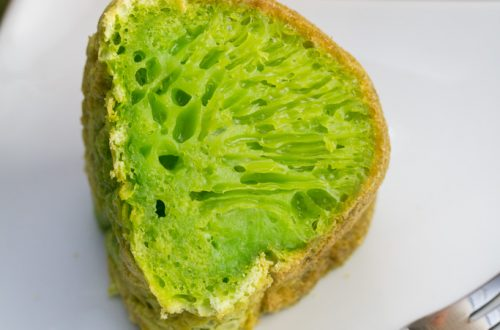 A slice of vibrant green Vietnamese honeycomb cake on a plate.