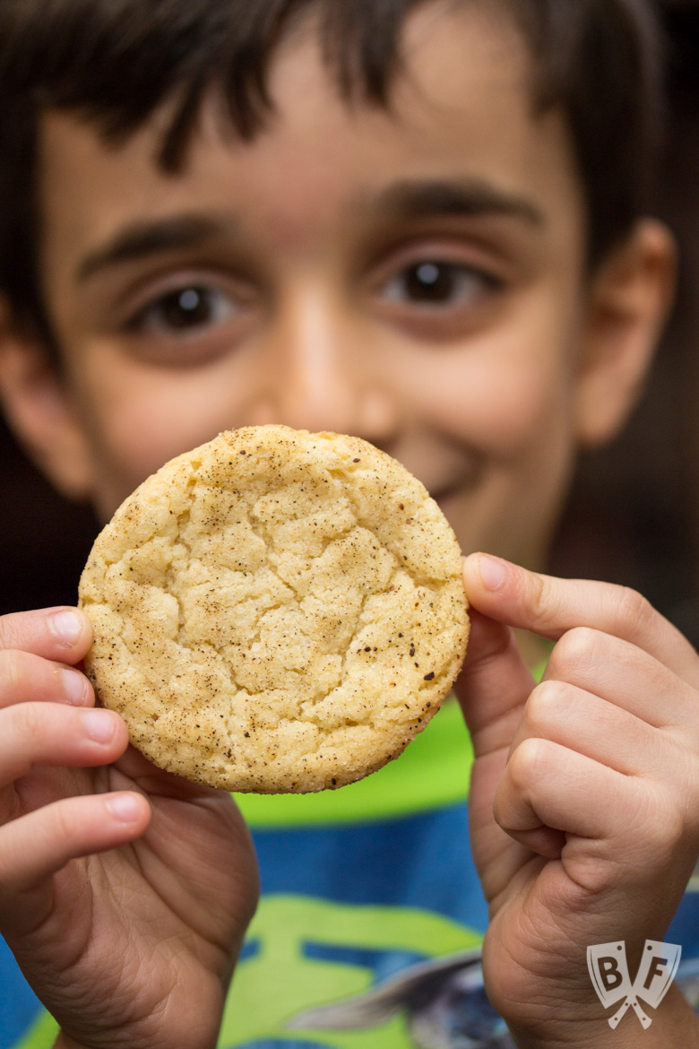 Close-up view of a child holding a Chai-Spiced Snicekerdoodle Cookie