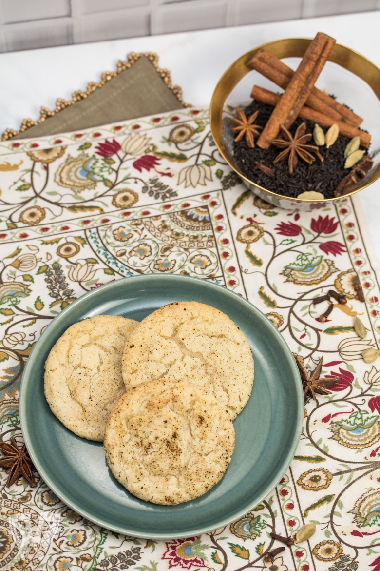 Overhead view of a plate of Chai Spiced Snickerdoodle Cookies with a bowl of whole spices in the background.
