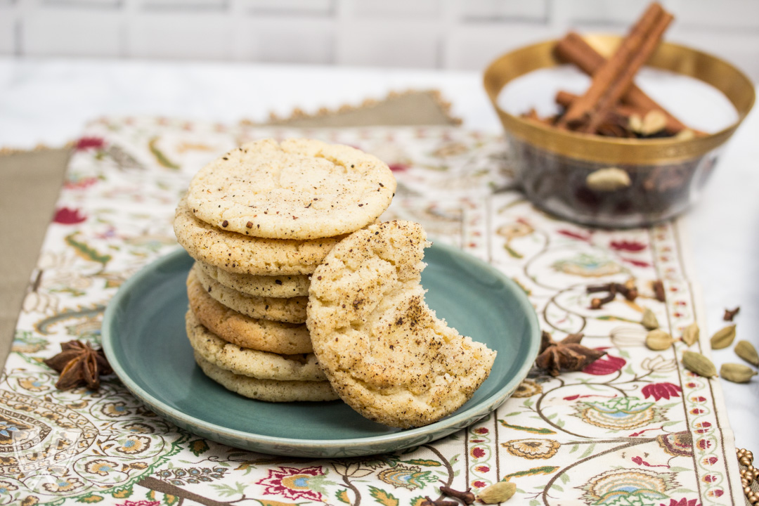3/4 view of a plate of Chai Spiced Snickerdoodle Cookies with a bowl of whole spices in the background.
