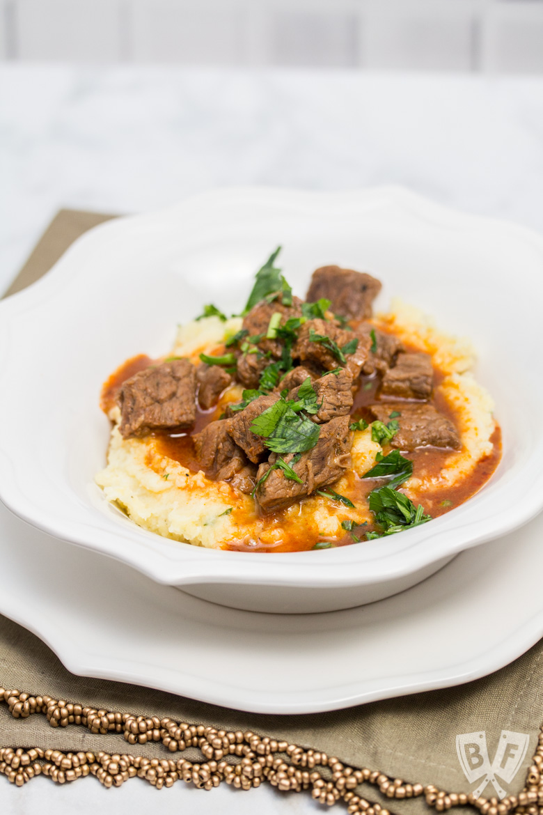 A heaping portion of mashed potatoes in a bowl with beef goulash poured over top, sprinkled with parsley.