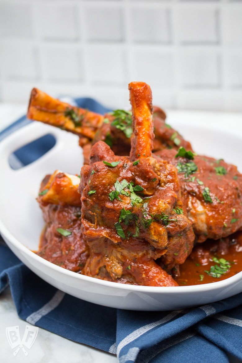 3/4 view of lamb shanks with tomato sauce sprinkled with parsley in a serving bowl.