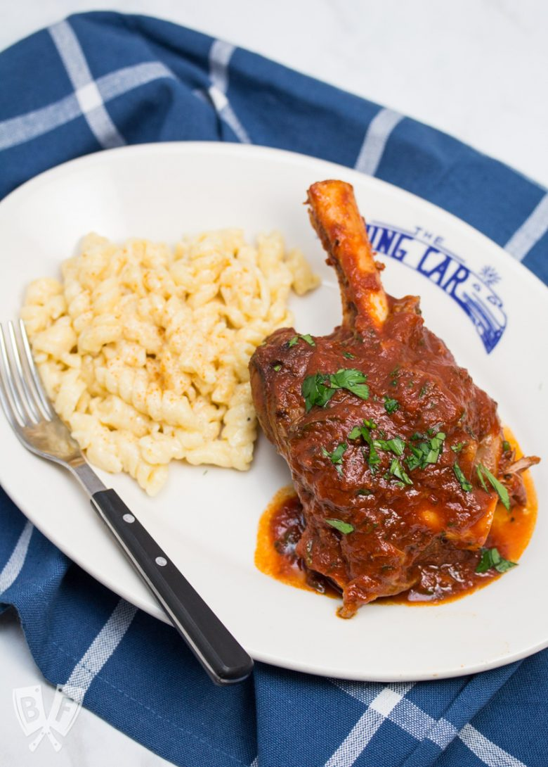 Overhead view of a plate with a lamb shank and tomato sauce next to macaroni and cheese with a fork on the plate.
