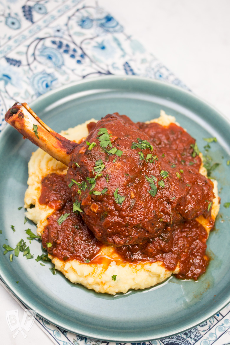 Overhead view of a plate with mashed potatoes topped with a lamb shank with tomato sauce sprinkled with parsley.
