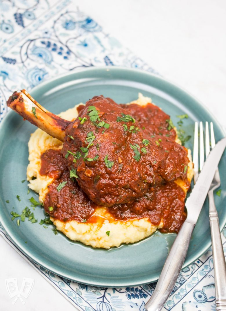 Overhead view of a plate with mashed potatoes topped with a lamb shank with tomato sauce sprinkled with parsley and fork and knife off to the side.