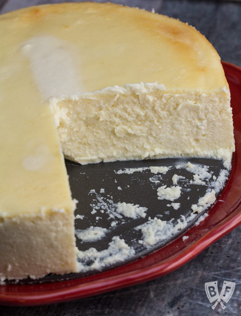 Overhead shot of a whole cheesecake with a slice taken out sitting on a red plate.