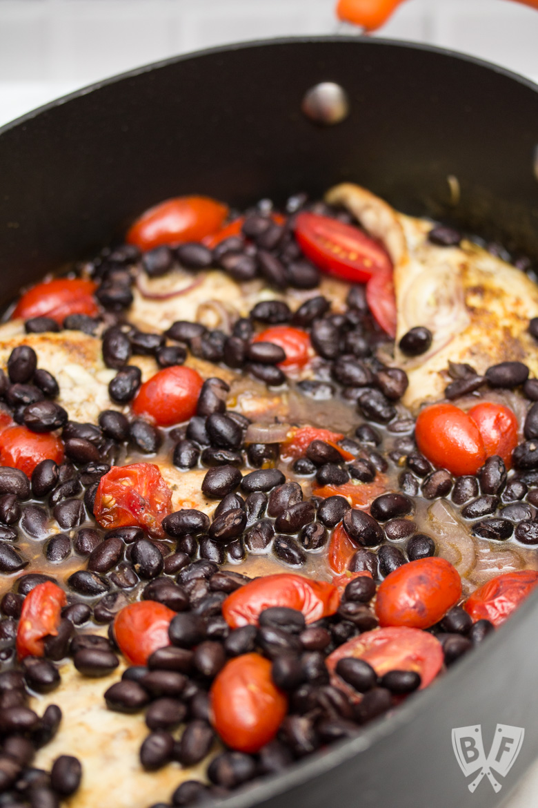 Close up of a Latin Chicken Skillet with Black Beans + Tomatoes.