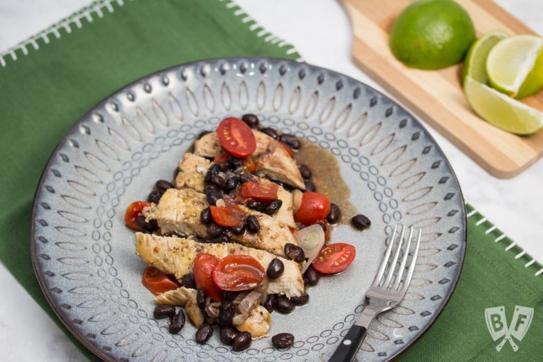 Overhead view of a plate of chicken with black beans and tomatoes with a lime cut up in the background.