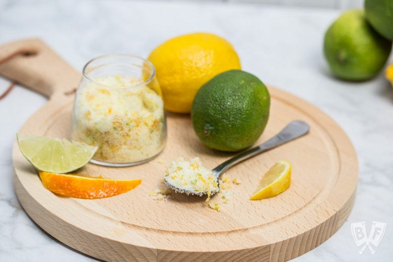 A round cutting board with fresh citrus and a spoon and jar full of a citrus zest, salt, and sugar mixture.