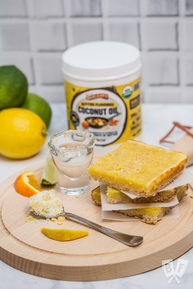 A stack of dessert bars with a shot of tequila, fresh citrus, and a jar of butter flavored coconut oil.