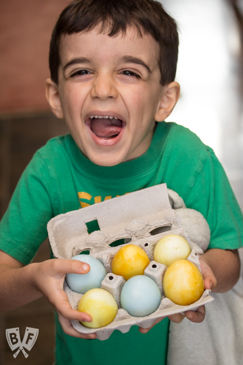 A boy holding a carton of naturally dyed Easter eggs.