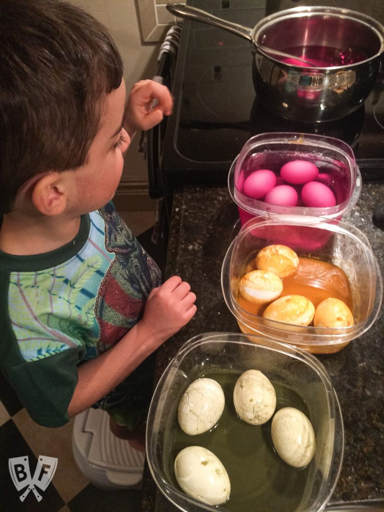 A child with bowls of Easter eggs soaking in natural egg dyes.