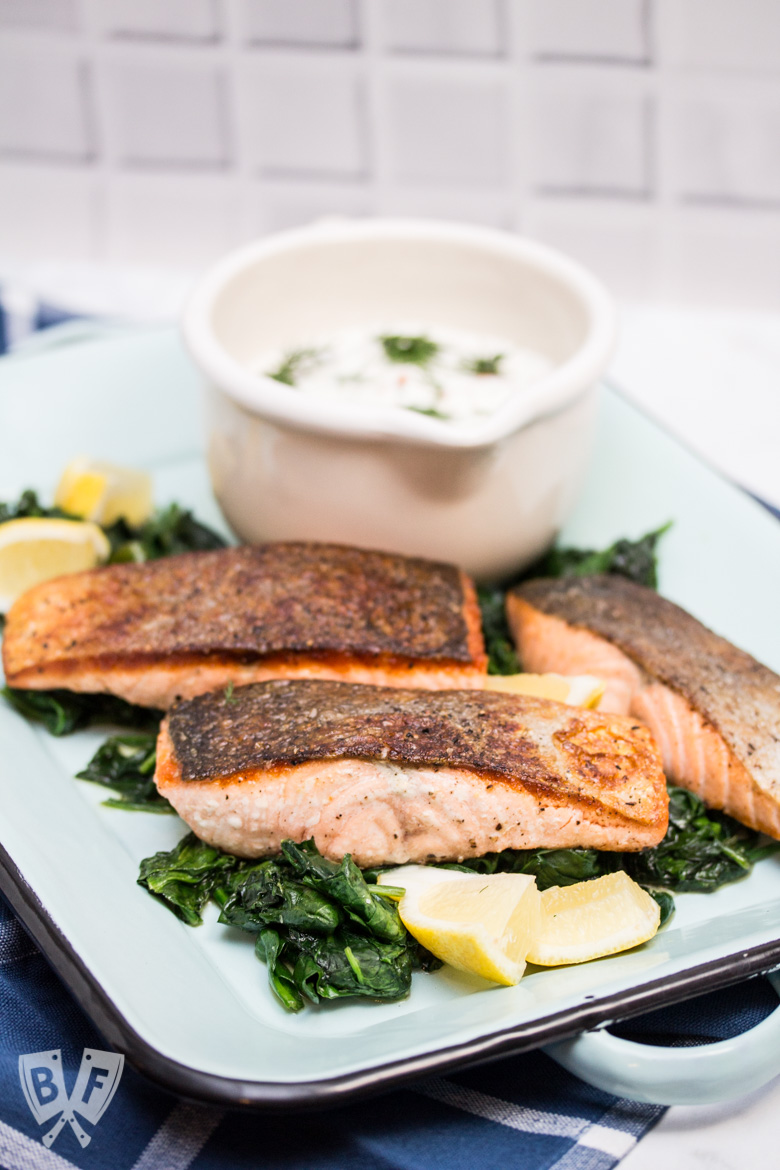 3/4 view of a platter of seared salmon on top of spinach and lemon wedges with a bowl of sauce in the background.