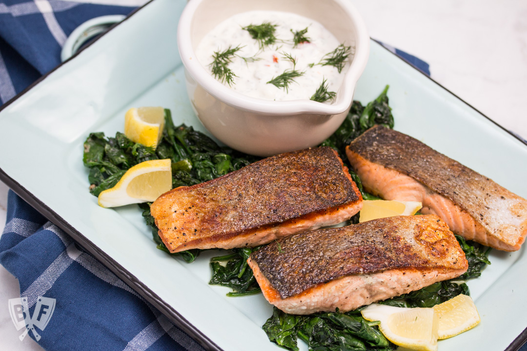 Overhead view of a platter of seared salmon on top of spinach and lemon wedges with a bowl of sauce in the background.